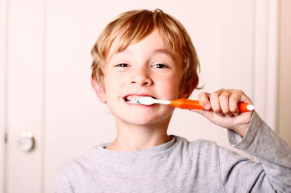 Boy brushing his teeth after receiving dental sealants.